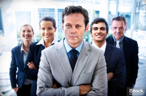 Portrait of a handsome business leader crossing his arms with his team standing behind him